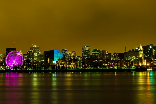 Longue exposition du Vieux-Montréal de nuit, prise à partir de l'île Sainte-Hélène. On reconnait la grande roue, l'horloge du quai, le Marché Bonsecours et les tours du centre-ville de Montréal.